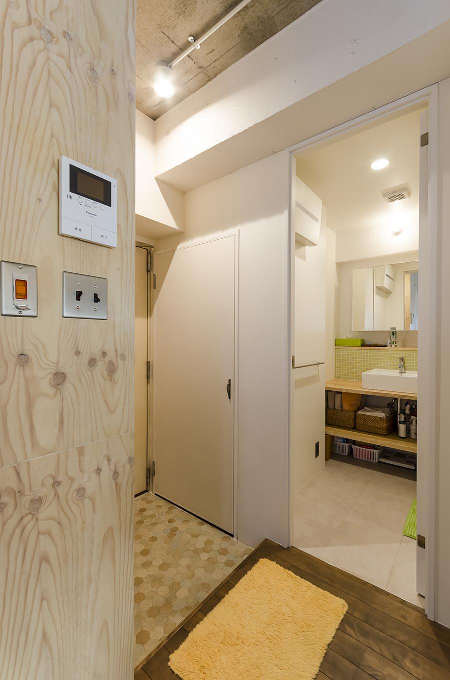 玄関の六角形のタイルと床の無垢材の組み合わせで迎えられる玄関。左手は洗面と浴室。