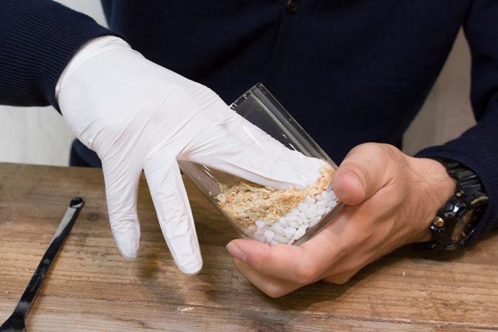 容器に水苔を入れ、指で押し固めるようにしながら傾斜をつけて入れる。ピートモスが砂利まで落ちないようにするフィルターの役目もあるので、しっかりと固める。