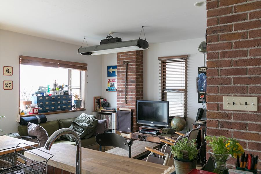 アンティークショップで購入した家具や、ご主人が長年収集した雑貨が並ぶリビング。柱に貼ったレンガがアクセントに。