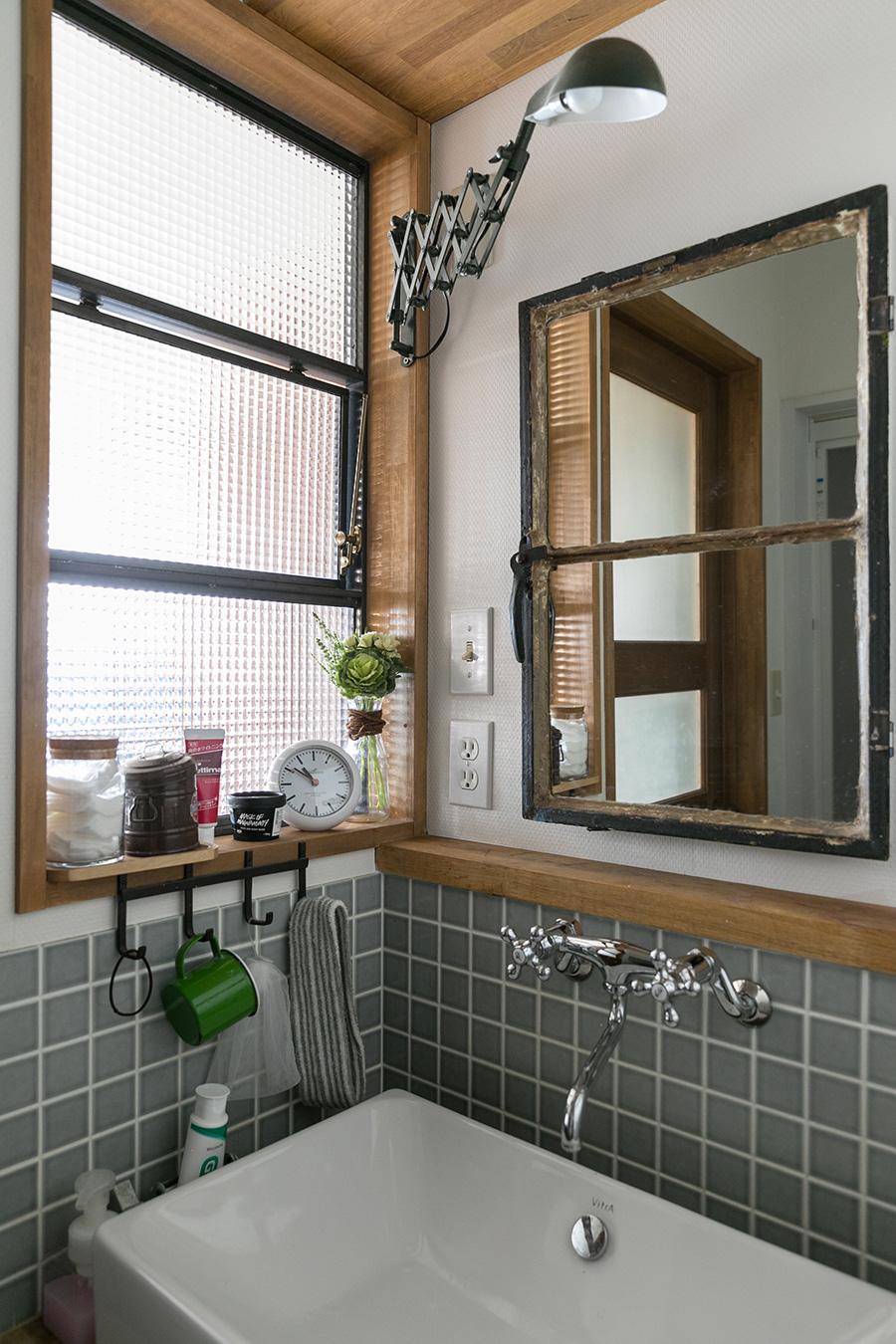 洗面台。古道具の鏡の後ろに収納棚を造作し、開閉できるように設計。