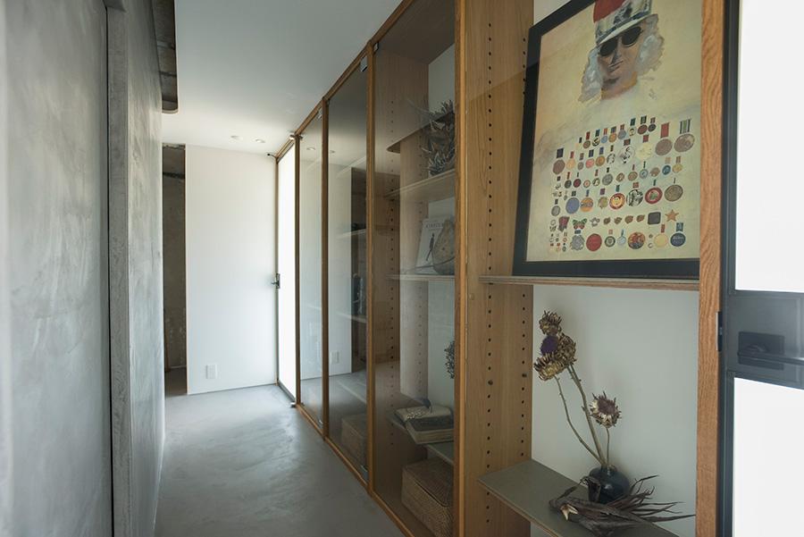 """唯一""""見せる""""部分を作った廊下の棚。ギャラリーやお気に入りのお花屋さんなどで選んだものが飾られている。将来はお子さんの収納棚としても活用する予定。"""