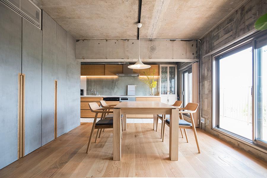 廊下の先に広がるのは、明るいLDK。むき出しのコンクリートと、廊下からつながるデコリエの味わいが調和する。無垢のオークの床が心地いい。ダイニングテーブルはベルギーのファニチャーブランドEthnicraft、イスはマルニ木工のHIROSHIMAシリーズ。