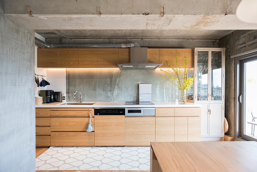 キッチンの壁は、コンクリートの手前にガラス板がはめ込まれている。油はねも防いで便利。天板にはサイルストーン(人工大理石)を使用した。