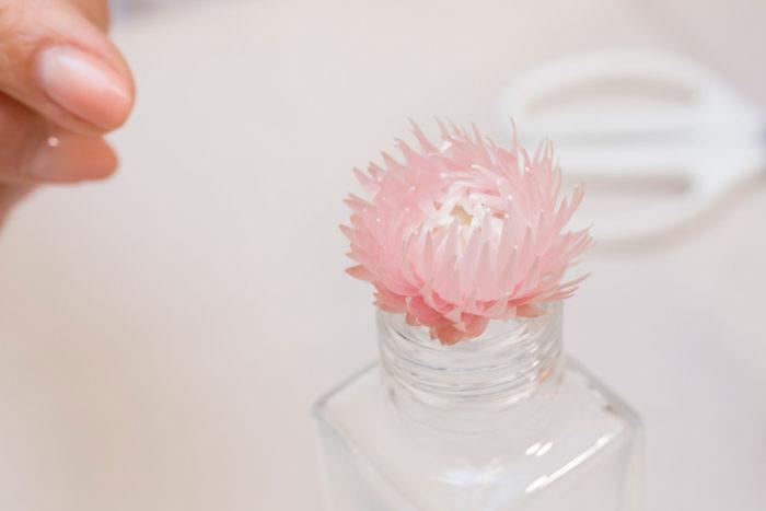 ボトルの口は意外と小さいので、花材の大きさに注意。これくらいの大きさのシルバーデイジーならキュッと押し込むことができる。