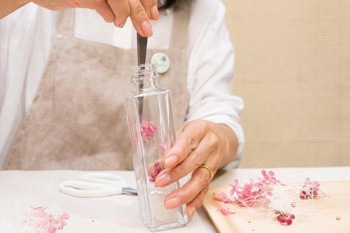 まずココナツファイバーを底に入れる。ピンセットで花材を優しく挟み、入れたい場所にセットする。