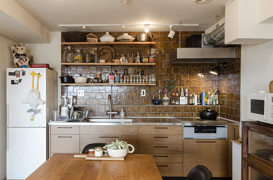 壁面にタイルを張ったキッチン。配管の都合でできた段差を調味料置き場として活用。