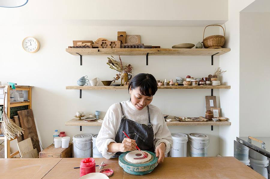 陶芸の作業をする奥さま。「棚は足場板を使って、自分で取り付けました」。