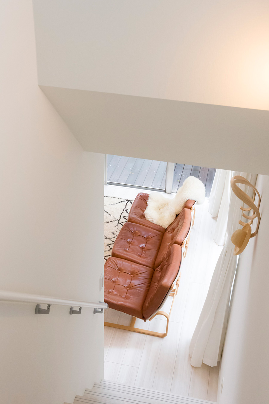 2階から階段を降り、リビングへ。曲げ木のコートハンガーはMOMAで購入。