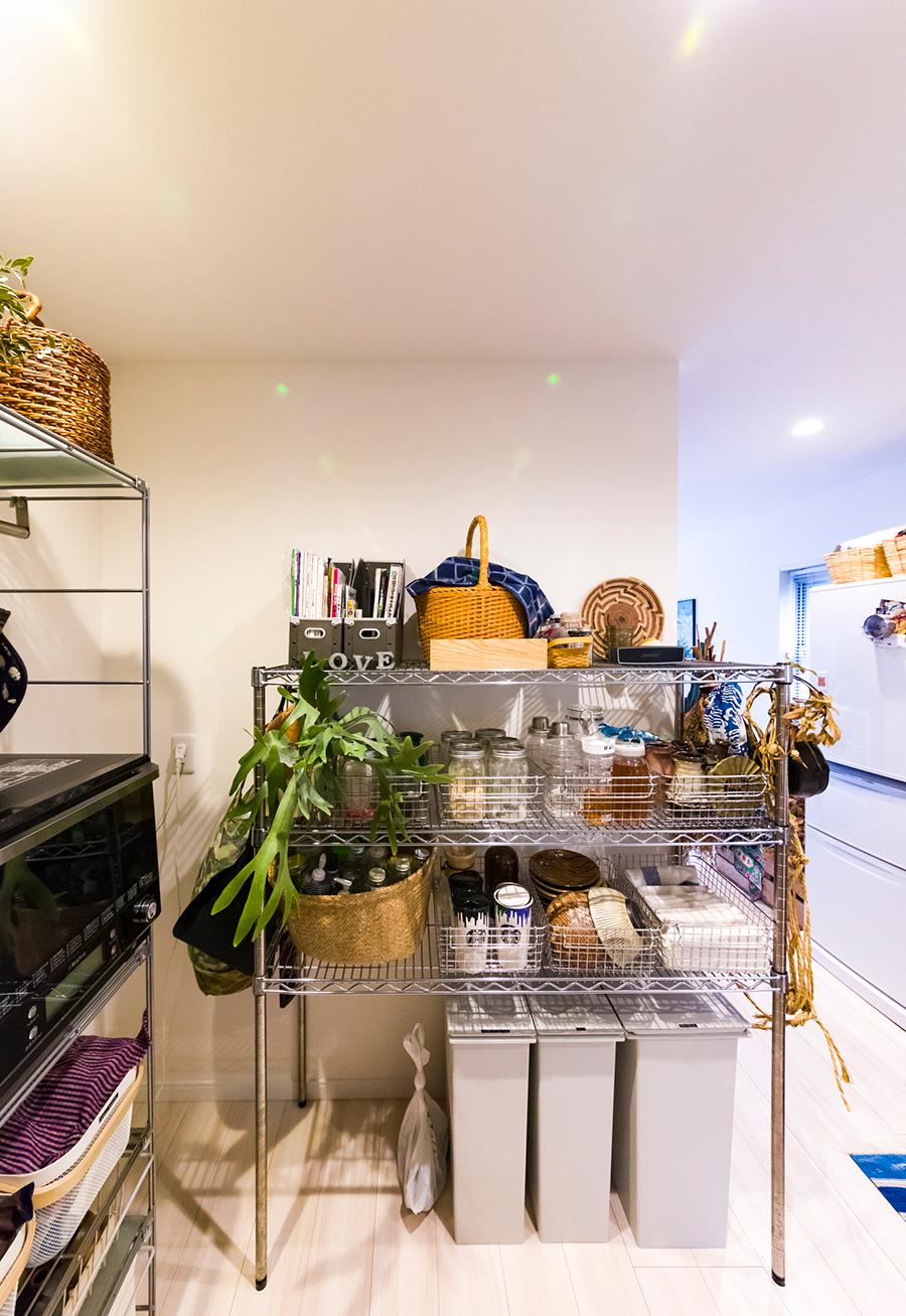 キッチン周りの小物の収納にはエレクター社のワイヤーラックを使っている。カゴに調味料などを小分けにして保管。ラックにコウモリランを吊るしてグリーンをプラス。