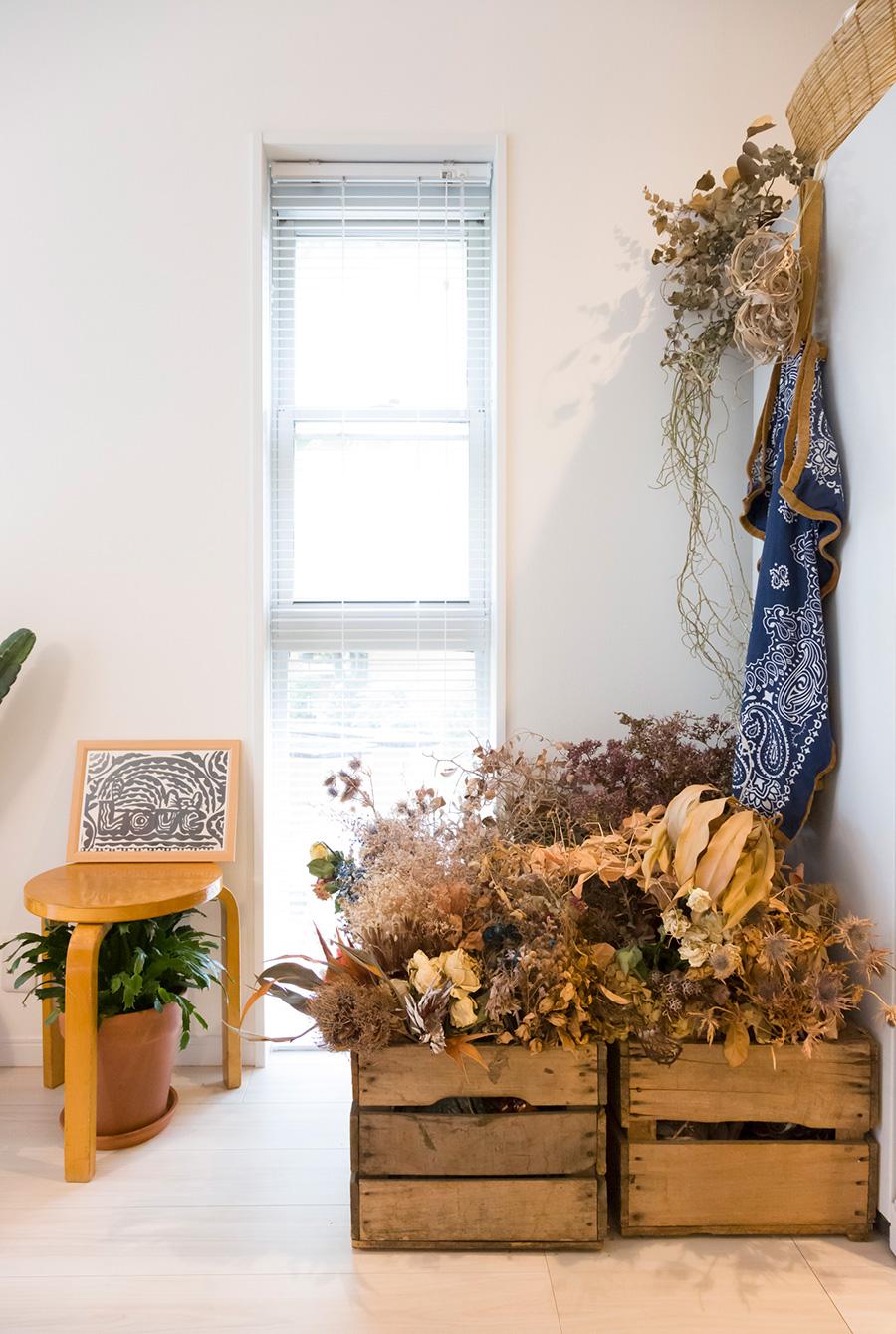 木箱にたっぷりとドライフラワーを入れて飾る。棚の上からも吊るして立体的に。