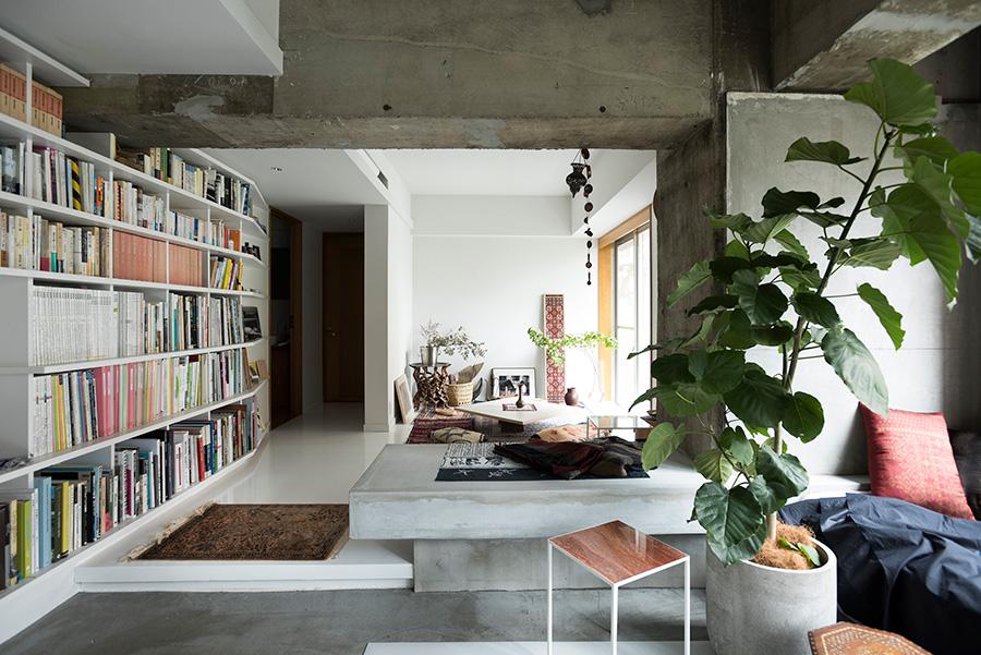 段差を上がるとプライベートエリアに。ベッドルームの入り口には、あえて厚めに設定した壁を新たに取り付け、短い廊下を設けてプライベート感を出した。「厚めにすることで重厚感を出し、ニッチも取り付けました」。たくさん所蔵する哲学書や作品集などを一括して収納できるよう、本棚も造作。