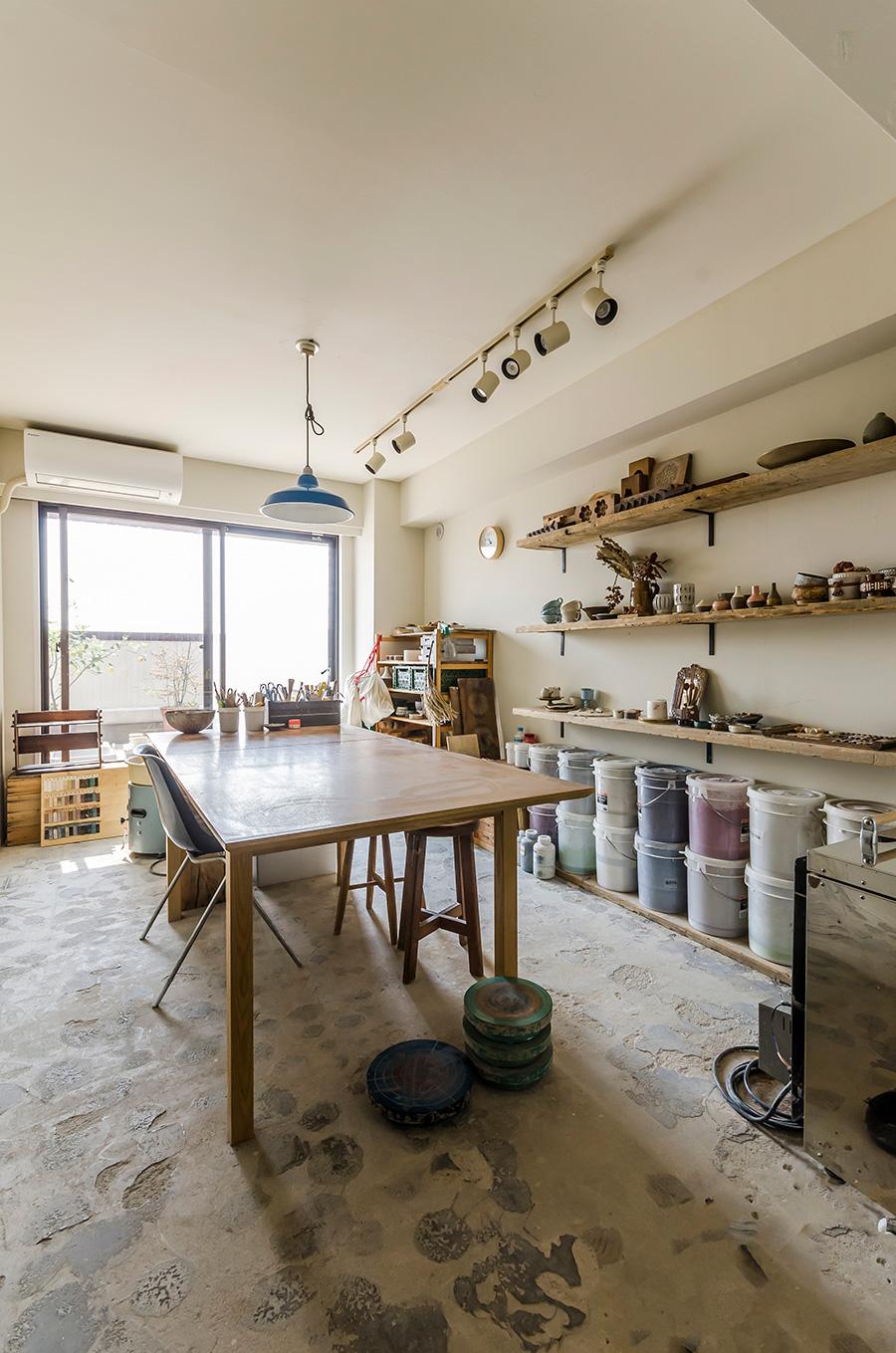 奥さまの作業場。コンクリート土間に陶芸の材料や工具などが置かれている。