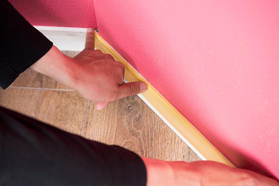 マスキングテープを15cm間隔くらいに始点と終点を決めて貼っていく。壁との間は1ミリくらい開けておくと、もとの壁の色が残りにくい。貼る度に指を左右にピーッと流して密着させよう。