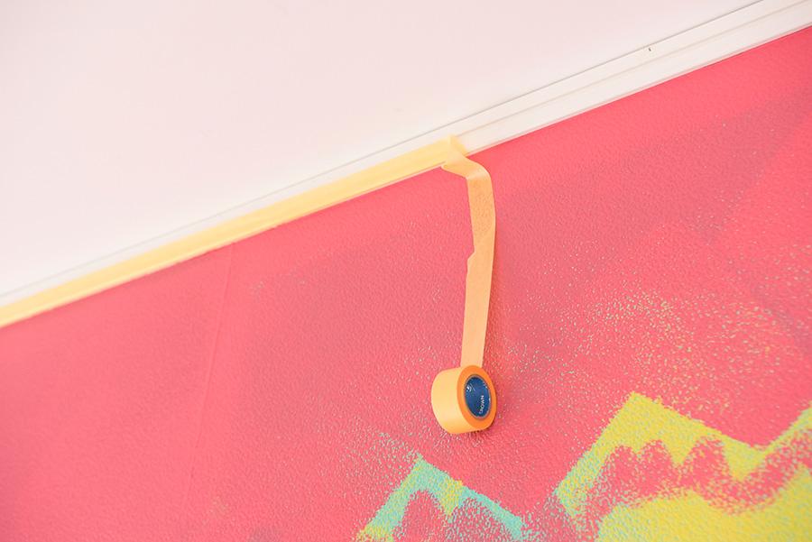 ここもポイント! 天井下は、脚立などを移動させて貼っていくので、手を放すときには一旦テープを壁に貼っておくこと。