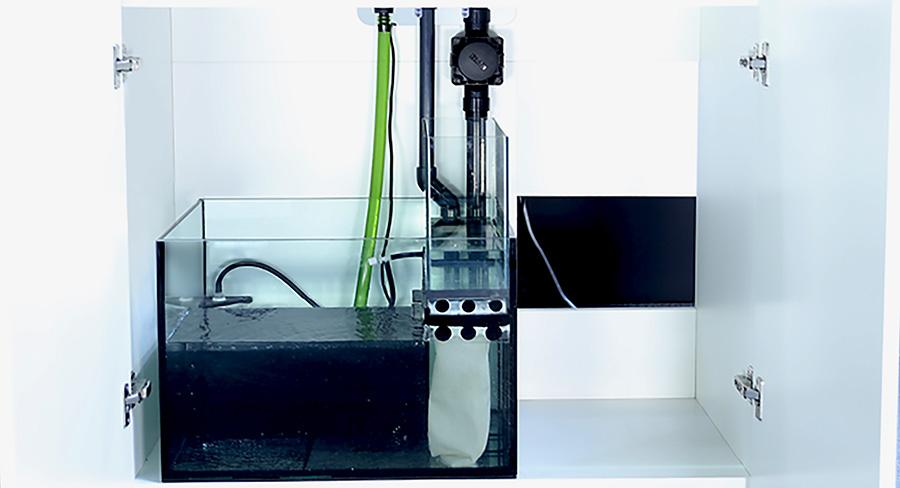 メイン水槽からオーバーフローした海水が、ミクロンフィルターバッグを通り、サンプに設置したプロテインスキマーで有機物を除去する。右側にはクーラーを置くスペースが空いている。