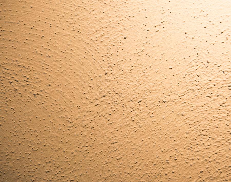 テクスチャーサンドという特殊な下塗り剤を塗り、乾いたところで砂粒を手で落とし、上から色を塗り重ねたもの。ローラーより刷毛がおすすめ。