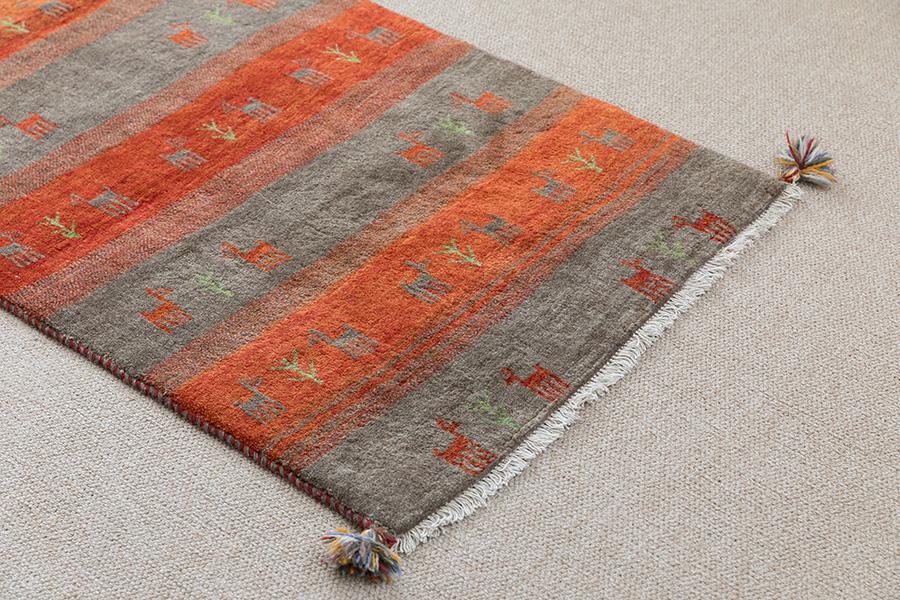 イランの遊牧民族・ガシュガイ族が織った「ギャッペ」。シンプルなインテリアに温かみのある小物をプラスするのがまきさん流。