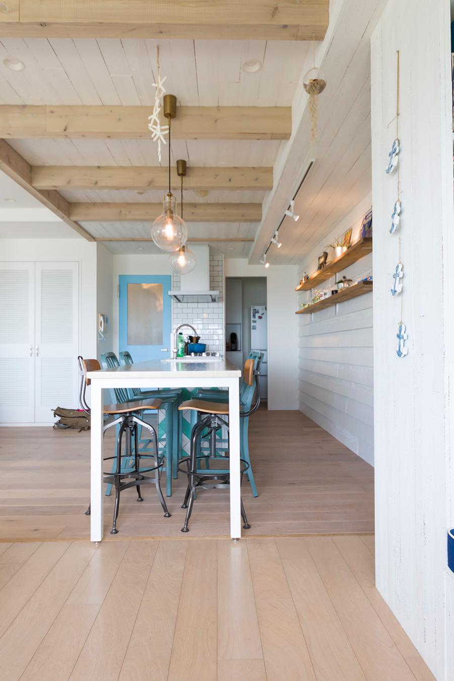 白にペイントした壁や天井の雰囲気がいい感じ。木の質感を残した天井の梁が引き立つ。ダイニングテーブルを兼ねた造作キッチン。