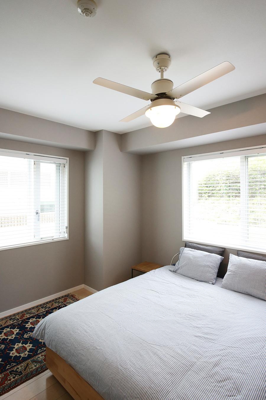 寝室の天井には、照明つきのシーリングファンを設置。壁は落ち着いたグレーに。