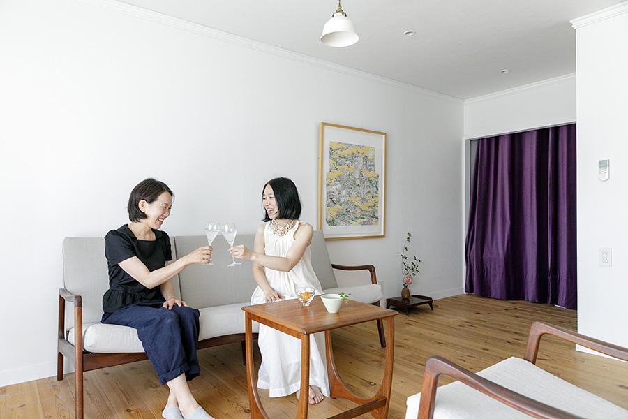 建築家の東端桐子さん(左)とUさん。奥の収納を隠す紫色のカーテンが部屋のアクセントになっている。