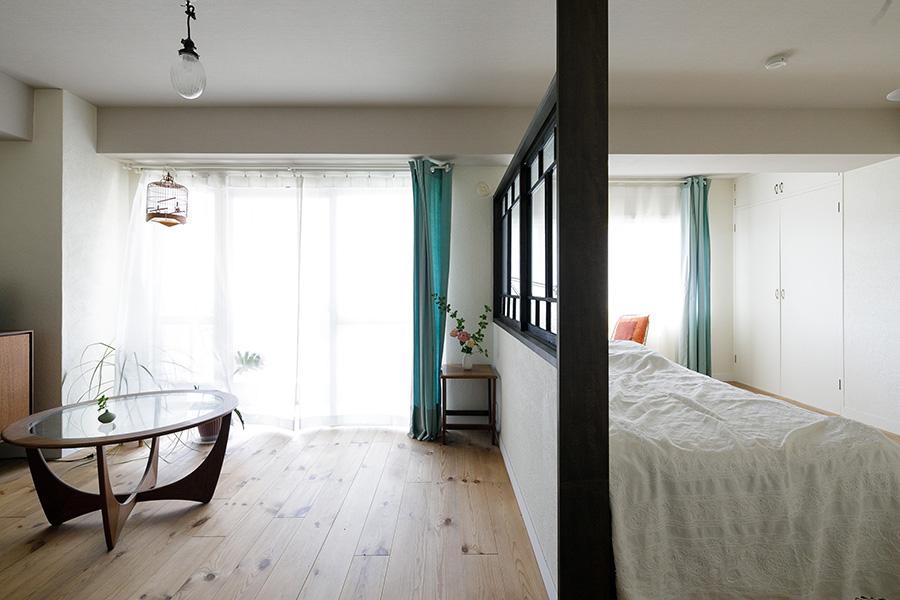 寝室はベッドスペースをキッチンと同じ古建具で仕切っている。