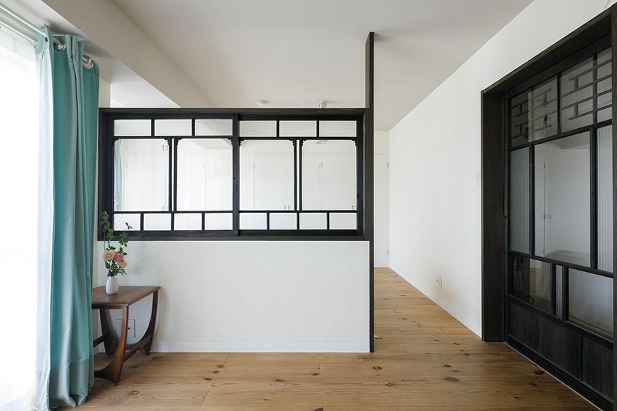 寝室入り口も、窓枠と同じ色合いの古い建具を入れて。各所にある濃い色の建具が空間をぐっと引き締めている。