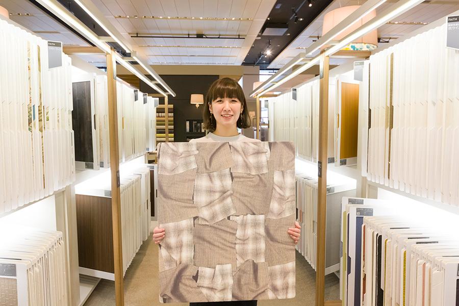 『サンゲツ』インテリア事業本部の小椋淑恵さんが手にしているのが『PHOTO CHECK』の壁紙のサンプル。「『サンゲツ品川ショールーム』では、実際に大判サイズの壁紙のサンプルを手にとってご覧いただけます。壁に貼ったイメージがつかみやすくなります。どうぞ足をお運びください」