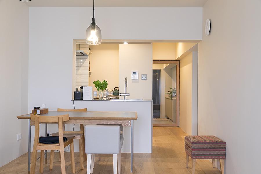 薄グレーの壁と無垢材の床に包まれたシンプルな室内。外せなかった梁を活かし、LD側に向けたオープンキッチンに変更した。