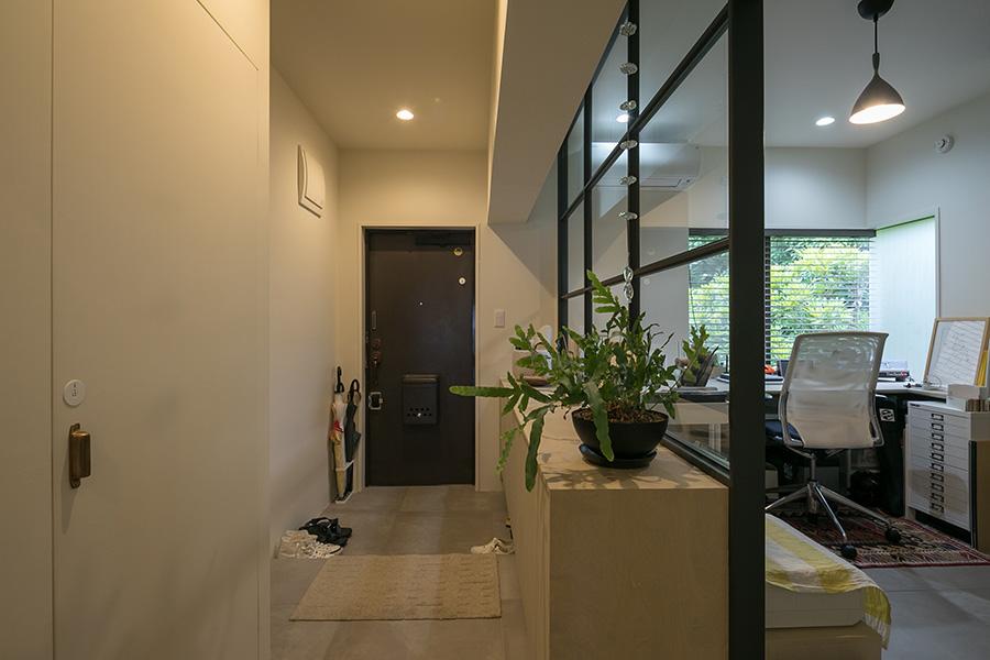 壁を壊しガラスの仕切りを採用することで、開放的になった玄関まわり。ガラスのフレームには木を使い、黒く塗装した。