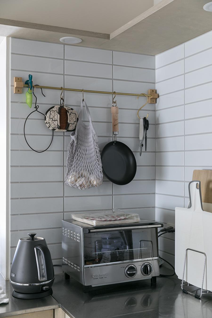キッチンツールは妻のこだわりでセレクト。フライパンなどを吊るすバーにも真鍮を使っている。