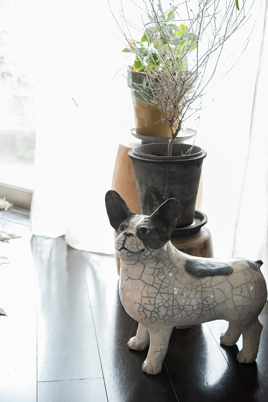 陶器製のフレンチブルドッグはH.P.DECOで売っていた作家もの。木でできた花台、リネンのカーテンがやさしい雰囲気。