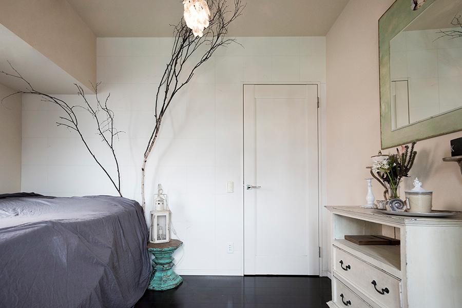 白とグレーのシンプルなベッドルーム。枯れ枝をディスプレイし、白い壁に映る影の美しさを楽しんでいる。