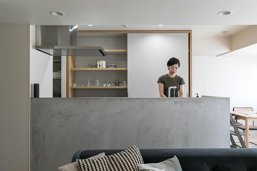 キッチンの周りはモルタル左官の壁で囲まれている。床が少し上がっているので、リビング側からは雑然としがちな手元も見えにくい。