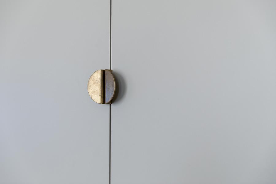 リビングの壁収納の扉は種々の色からこのグレーを選び、真鍮の引手を。こちらも「BP.」オリジナル。