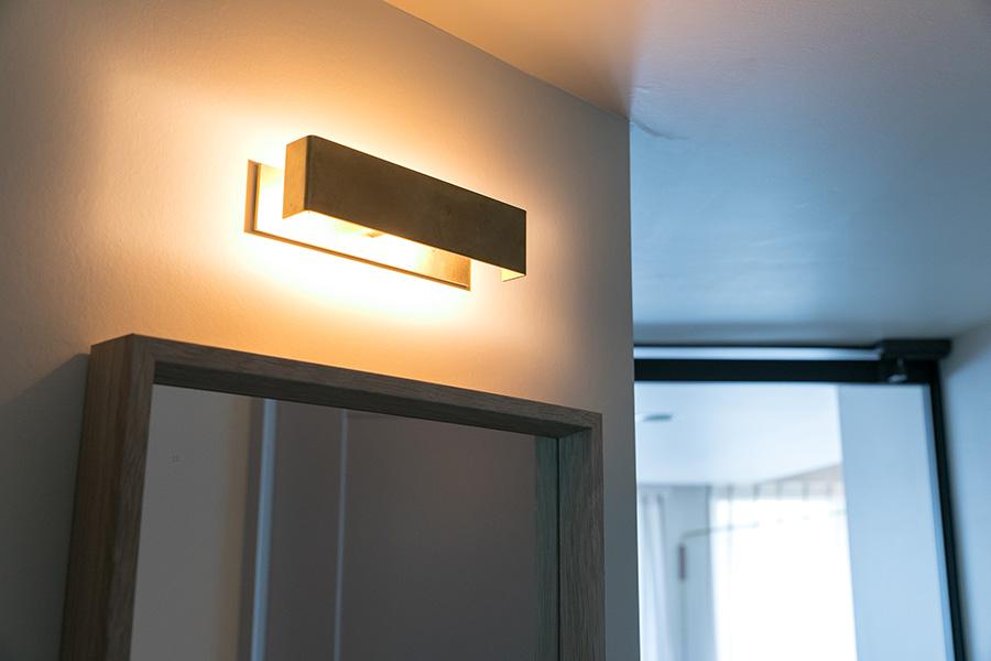 玄関のミラー上の照明も特注で。出かける前に身だしなみを整えるのにぴったりな端正なデザイン。