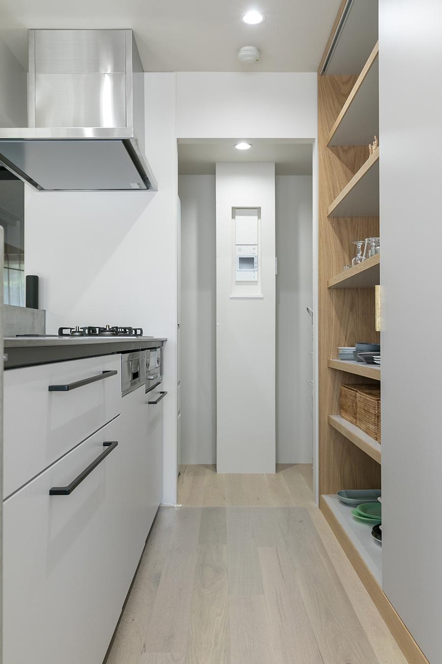 キッチンは「TOTO」に、「AEG」の食洗機を組み合わせた。キッチンパネルも薄いグレーを。後ろの収納棚はオーク材で、手前には電子レンジやゴミ箱などを。奥はパントリー。