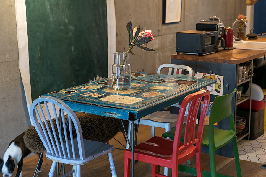 ブルーのダイニングテーブルを、色とりどりの個性的なチェアが囲む。