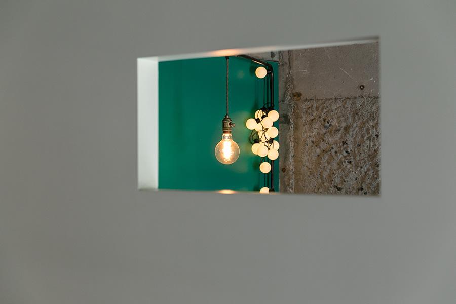壁の四角い窓から、寝室のグリーンの壁や、台湾で買ったというボールが連なるキュートなLED照明が覗く。