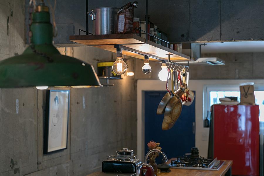 キッチンの上の照明は、ひとつづつ違う電球で表情を楽しむ。ダイニングテーブルの上のペンダントライトは琺瑯製のアンティーク。