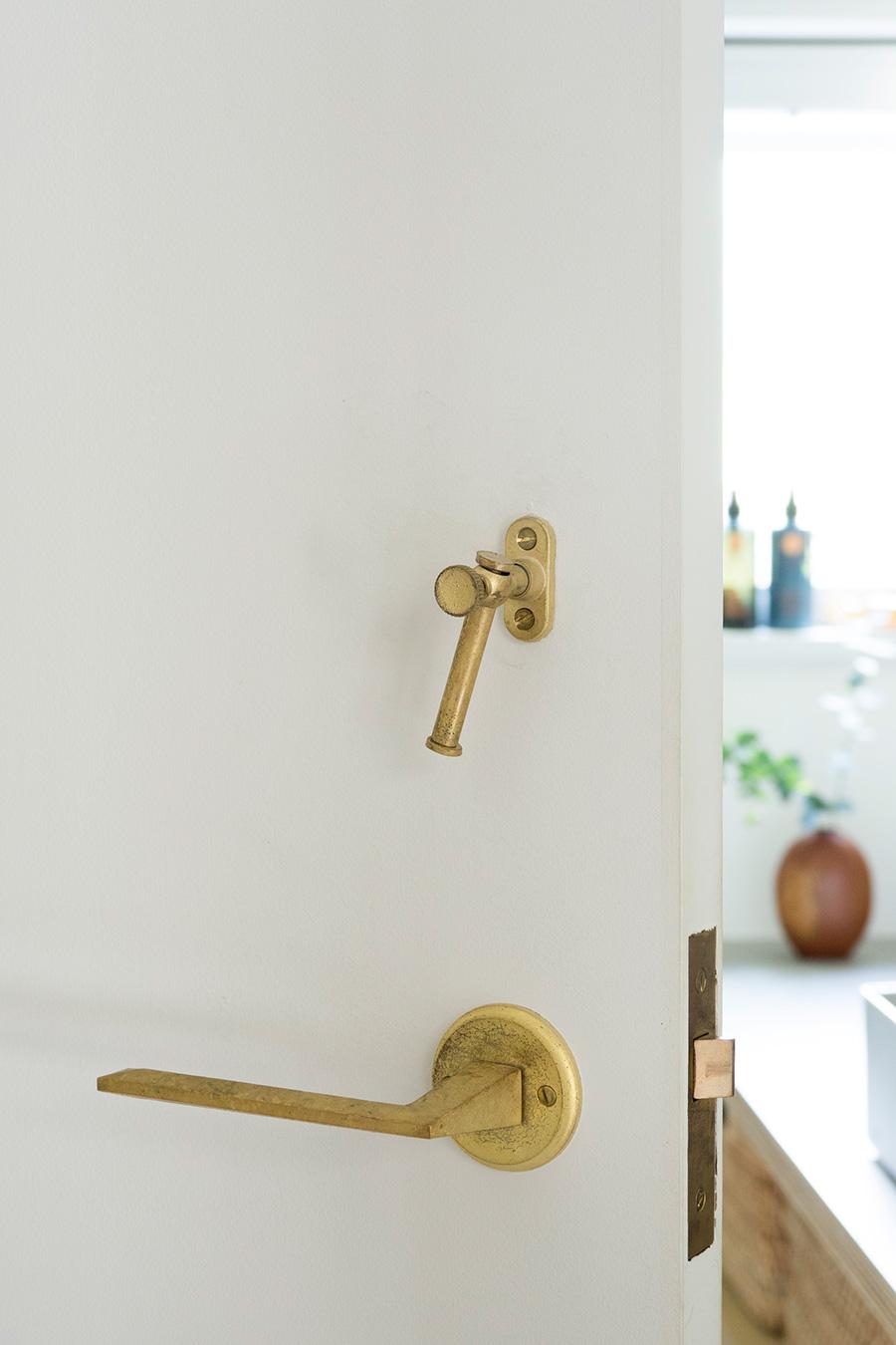 バスルームのドアの取っ手や鍵に真鍮を採用。味のある光沢感がシンプルな空間に趣きを添える。