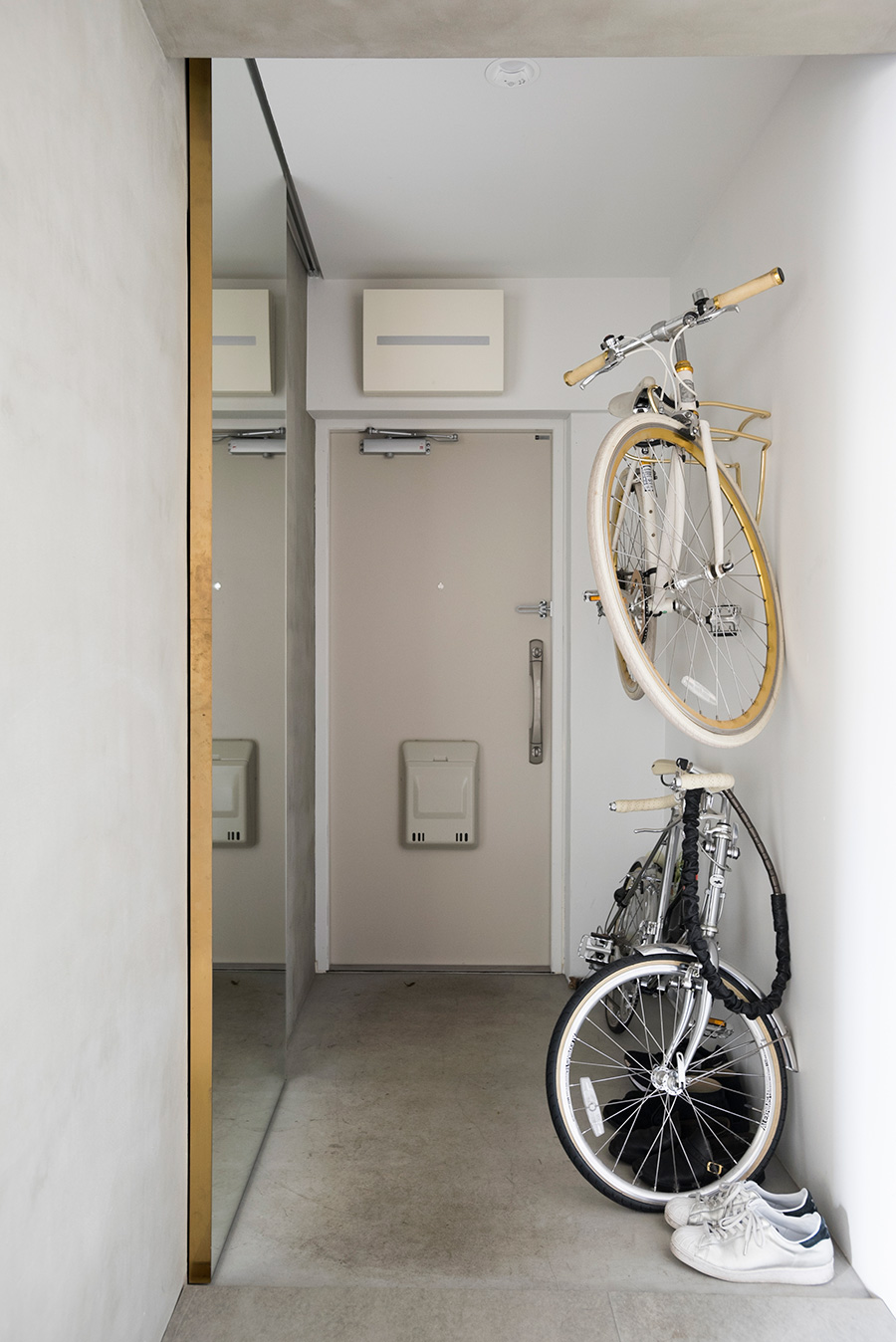 玄関のシューズクローゼットには、姿見を兼ねた引き戸を。真鍮がさり気なくあしらわれている。