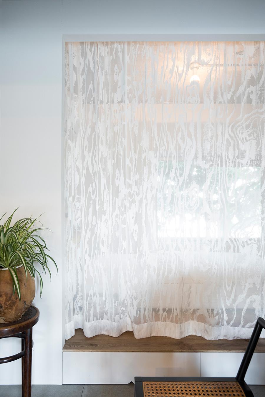 180910oga-015ベッドルームを間仕切るカーテンは、友紀さんがデザインしたもの。木材をスキャンして木目を柄に出した。レースのような繊細さ。