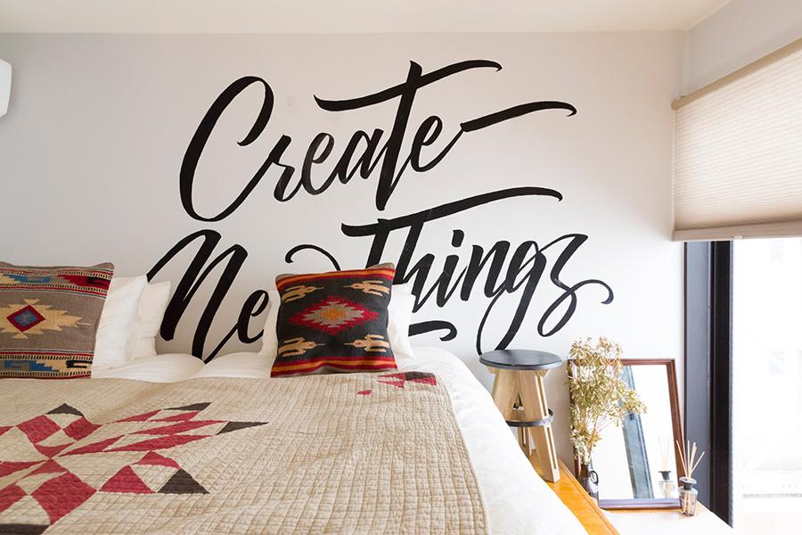 壁には井澤さんが描いた大胆なサインペインティング。オルテガパターンのクッションやベッドカバーとの相性も抜群。