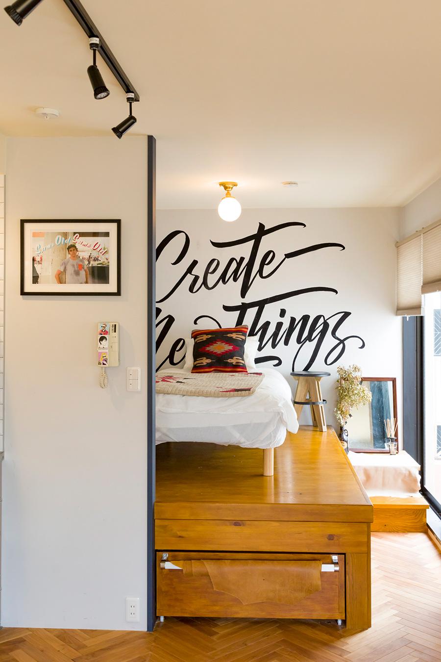 ベッドは階段を2段上がった場所に置かれている。床下は引き出し式の収納庫になっている。左の写真+サインペインティング作品は井澤さんが制作したもの。