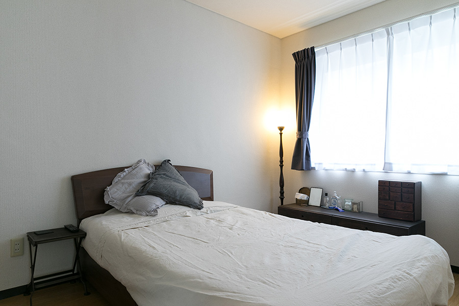 寝室も間接照明でほの暗く落ち着く空間に。テレビなどはこちらの部屋で観る。照明や棚も古いもので。