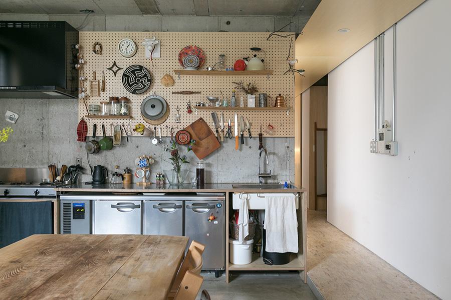 キッチンカウンターの下に業務用の冷蔵庫を収納。コンロは三口の『ガスクッカー』。廊下は一段高いOSB合板と天井にシナ合板、キッチンとリビングはモルタル仕上げにして、空間をゆるやかに分けている。