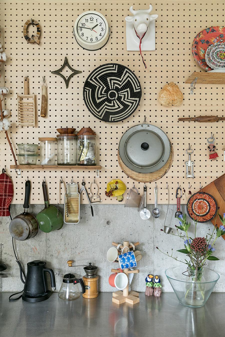 キッチンの壁には有孔ボードを。道具を収納できる機能性だけではなく、ディスプレイも楽しめる。「棚は自分でつけました。蟹の甲羅は好きでつい飾ってしまうアイテムです。金沢土産の蟹です(笑)」