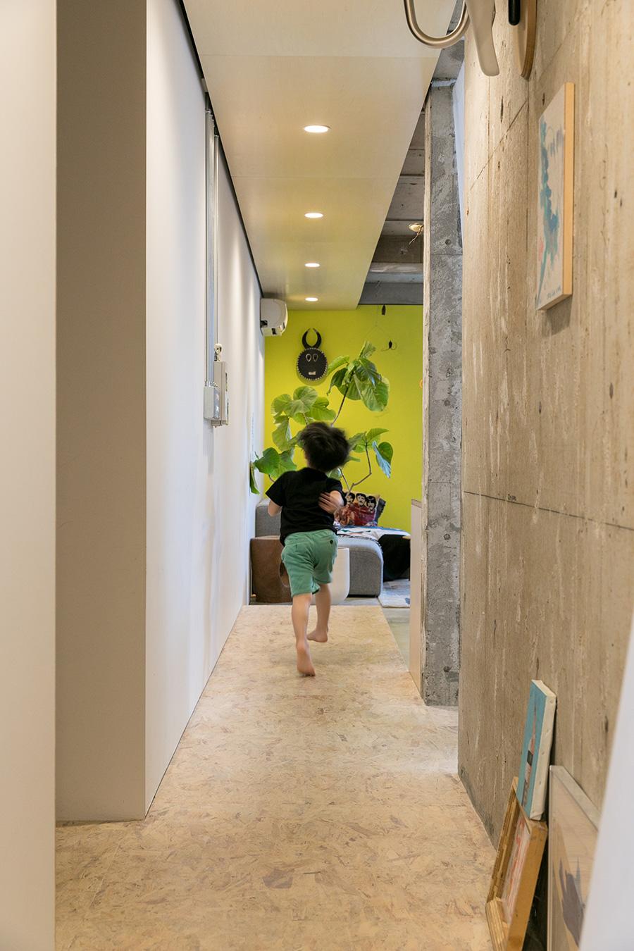 仕事場からリビングへ。OSB合板がリビングの中央まで延長することで、空間に連続性が生まれている。