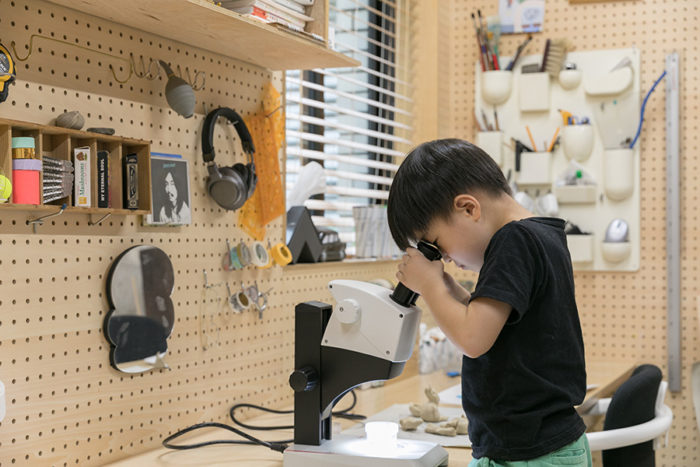 慶子さんの横で顕微鏡を覗く究くん。有孔ボードは、仕事道具を機能的に配置できる。
