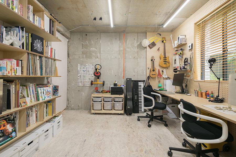 奥が賢策さんのスペース。有効ボードを活用して、壁にギターを飾っている。イスはヴィトラのオールスター。照明は、照明デザイナーの岡安泉さんが制作。